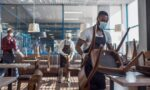 Multiethnic staff in facial masks preparing restaurant for reopening after quarantine. Young waiters in aprons protective masks and gloves arranging furniture in cafe before open